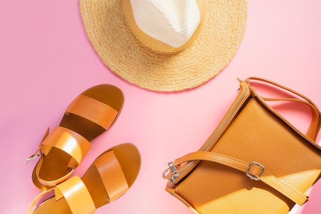 O molde com sandálias de couro marrons, chapéu de palha e areia colore o saco no fundo cor-de-rosa. acessórios femininos. conceito de férias de viagens de verão. kit de venda copie o espaço.
