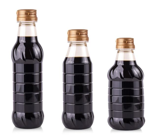 O molho de soja em garrafas de plástico, isolado no fundo branco.
