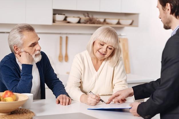 O momento de assinar o acordo. casal sênior positivo e decisivo sentado em casa conversando com o consultor da previdência social enquanto assina o acordo