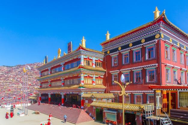 O monastério vermelho em larung gar (academia budista) no dia e no fundo do sol é céu azul, sichuan, china