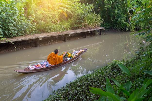 O monge está remando no canal, tailândia. modo de vida budista, turismo natural