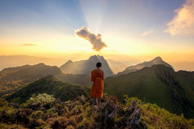O monge novato caminhou no topo da colina para olhar o sol brilhando em luz dourada