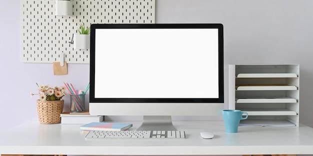 O monitor do computador está colocando em uma mesa de trabalho branca, cercada por equipamentos de escritório.