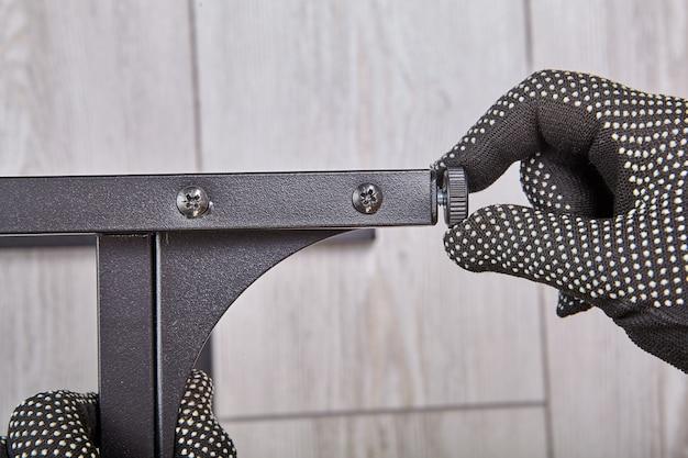 O montador de móveis instala a arruela para ajustar as pernas.