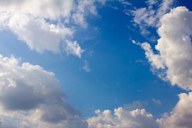 O montão branco nubla-se no céu azul no dia de verão.