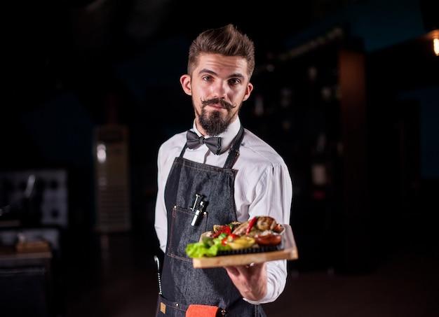 O mordomo de bigode segura o prato com o prato preparado em um evento festivo.