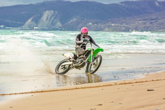 O motociclista com traje de proteção anda de motocicleta no mar, respingos voam sob as rodas.