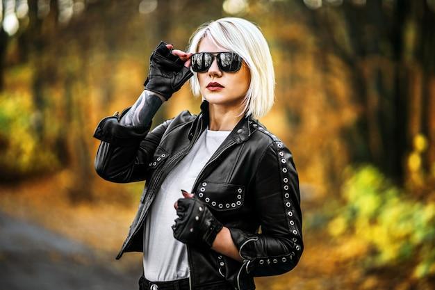 O motociclista consideravelmente louro denominou mulheres na jaqueta de couro preta com os óculos de sol que estão ao ar livre na floresta
