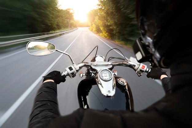 O motociclista está andando pela estrada de asfalto vazia à noite