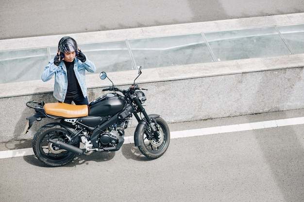 O motociclista parou na rodovia, ele está parado ao lado de sua motocicleta e tirando o capacete
