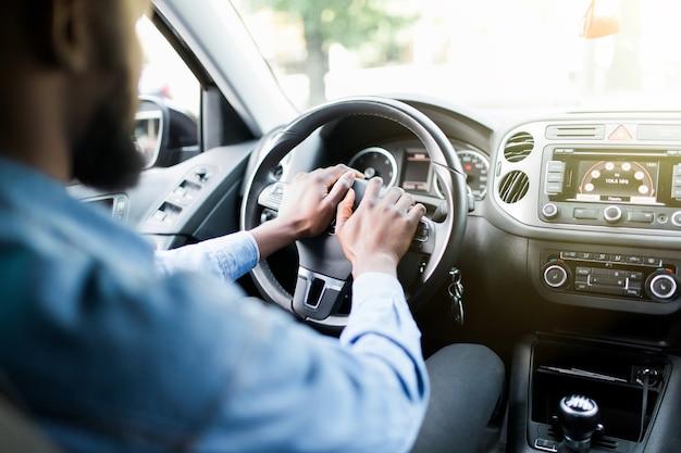 O motorista africano agressivo com raiva apita e grita no carro
