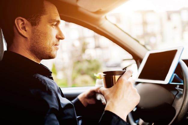 O motorista assiste a filmes ou programas de tv no tablet durante o almoço. parando para comer algo. homem comer lanche no carro e bebe café ou chá.
