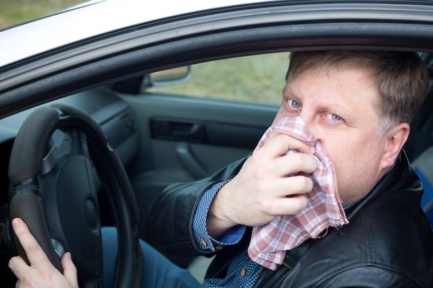 O motorista cobriu o nariz com um lenço dos gases fortes da poluição do ar automotivo.
