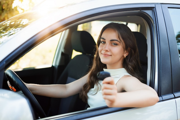O motorista da mulher feliz se gabava de receber a carteira de motorista mostrando a chave do carro e se sentindo feliz e com alto espírito. garota jovem estudante tem seu primeiro carro