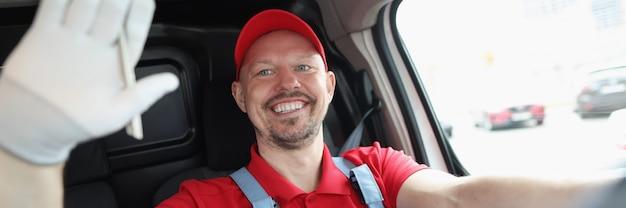O motorista de correio masculino sorridente acena com a mão enquanto dirige