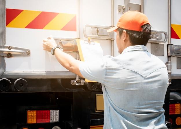 O motorista do caminhão está fechando a porta do contêiner.