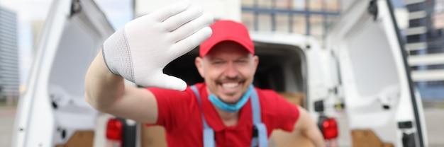 O motorista do correio uniformizado está sorrindo e acenando segurando a caixa corton