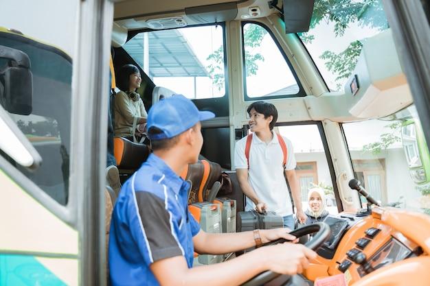 O motorista do ônibus se virou e viu um passageiro asiático carregando uma mala pela porta enquanto entrava no ônibus