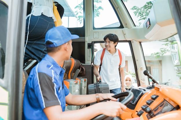 O motorista do ônibus se virou para ver um passageiro do sexo masculino carregando uma mala a bordo do ônibus