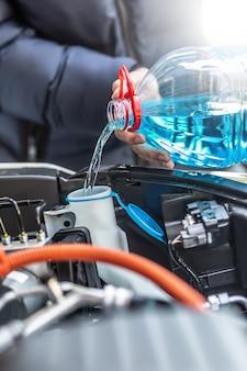 O motorista do sexo masculino derrama anticongelante no tanque para borrifar o para-brisa.