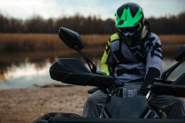 O motorista está sentado em uma moto-quatro
