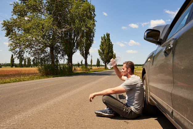O motorista está sentado na estrada, perto de um carro com o capô aberto e uma garrafa de água em um dia quente e ensolarado.