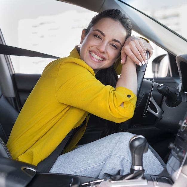 O motorista sorri e encostado no volante