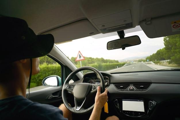 O motorista viaja em seu carro na rodovia, vista de dentro do carro. mãos no volante, clima frio de verão