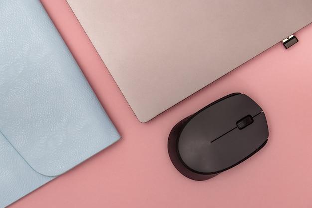 O mouse sem fio próximo acima com usb conecta no fundo rosa com laptop fechado e caixa azul. espaço de trabalho criativo. conceito de educação. postura plana.