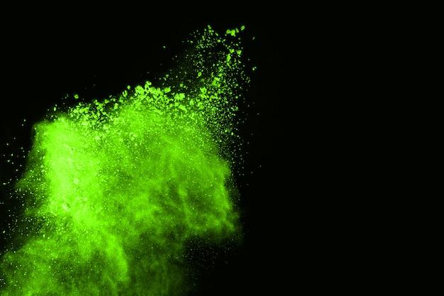 O movimento da explosão de poeira abstrata congelou o verde no fundo preto.