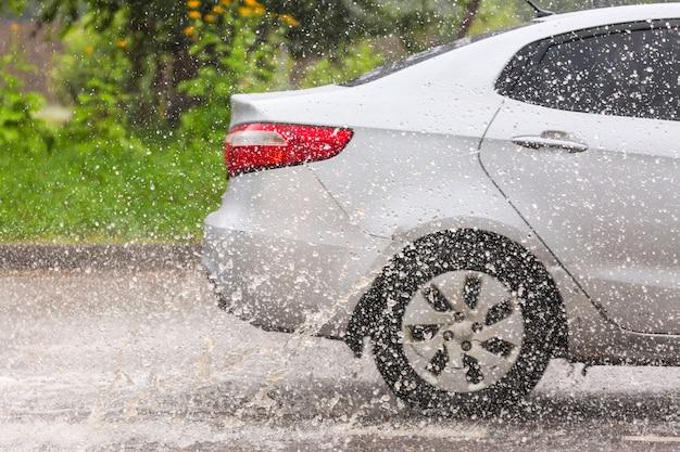 O movimento do carro através da grande poça de água espirra das rodas na estrada da rua