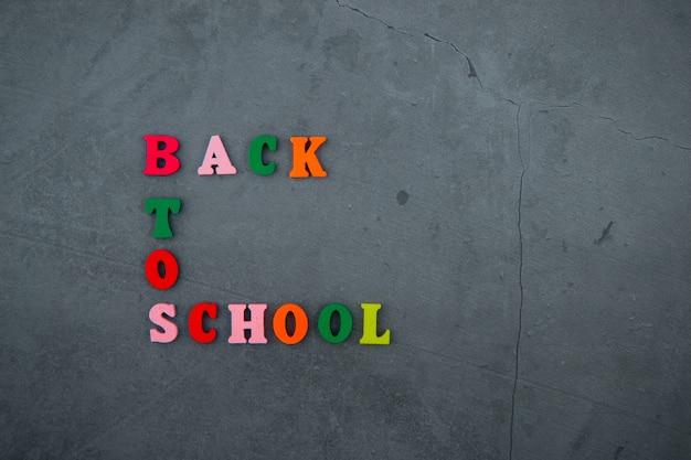 O multicolorido de volta à palavra escola é feito de letras de madeira em uma parede rebocada cinza.