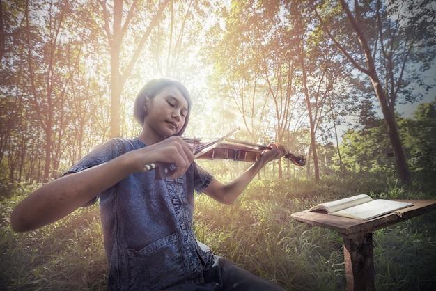 O musical: pequena criança asiática tocando violino ao ar livre