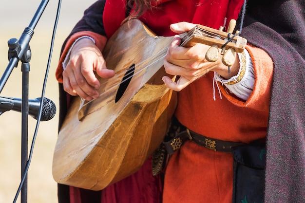 O músico executa uma melodia em um instrumento musical medieval dedilhada que se assemelha a um bandolim ou alaúde_