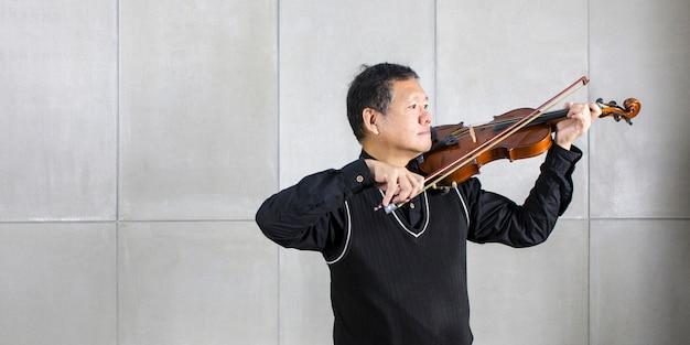 O músico que joga o violino na sala de estar relaxa o tempo.