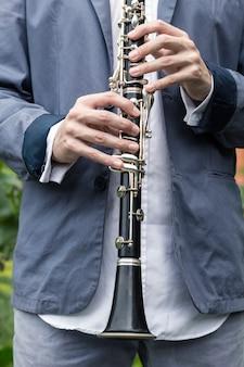 O músico segura um clarinete nas mãos.