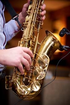 O músico toca jazz no saxofone.