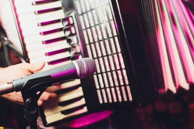 O músico toca o microfone close-up acordeão.