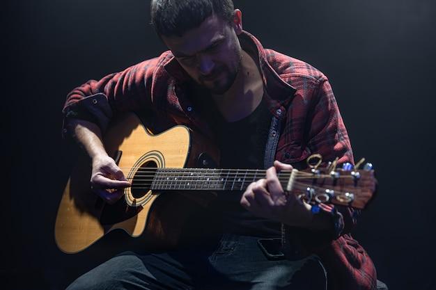 O músico toca violão sentado em uma sala escura.