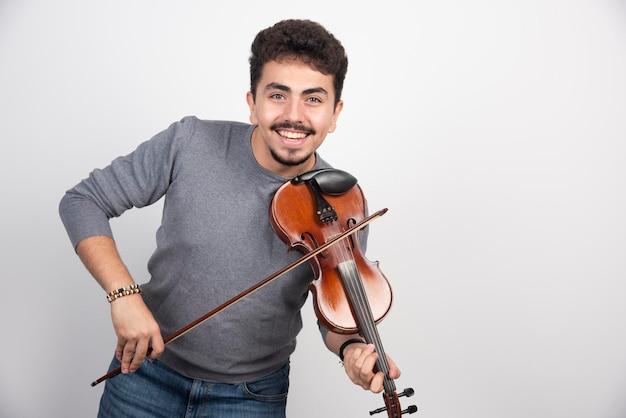 O músico toca violino e parece inspirado e positivo.