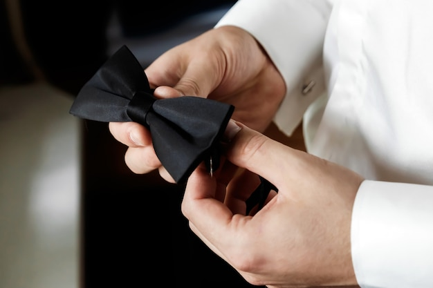 O muzhchin, uma camisa branca com calças largas e escuras e elegantes, segura um bowknot de borboleta