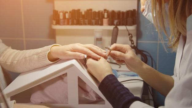 O nail master trata a cutícula de uma jovem cliente com uma pinça de manicure em um salão de beleza, luz solar.