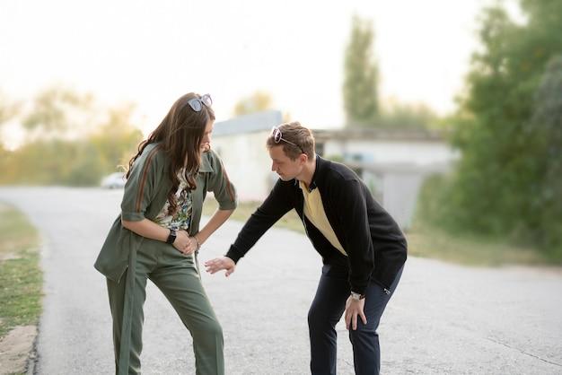 O namorado e a namorada chateados sentindo dor e ajuda, jovem casal ao ar livre