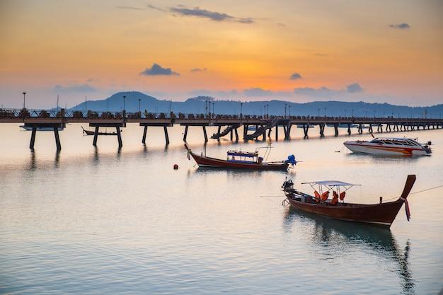 O nascer do sol bonito e as paisagens do cais da ponte de madeira com os barcos durante o verão do nascer do sol viajam em phuket, tailândia.