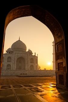 O nascer do sol de taj mahal através de uma arcada em agra india disparou no iso alto.
