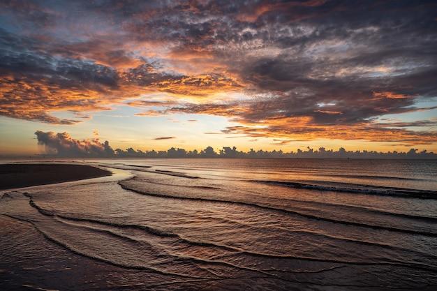 O nascer do sol disparou sobre o mar e uma bela nuvem.