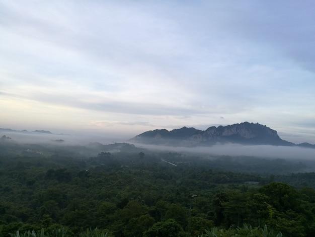 O nascer do sol está chegando sobre as montanhas, a luz do sol se sobrepõe ao céu azul pela manhã