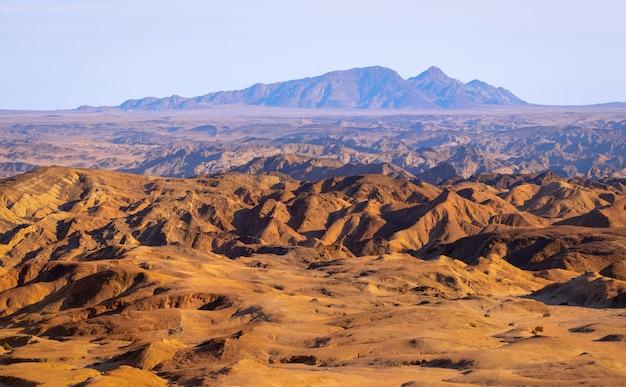 O nascer do sol ilumina o vale da lua amarela. paisagem do deserto na áfrica. namibia