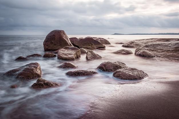 O nascer do sol sobre o mar balança no bech. águas lisas, efeito extrusor longo. seascape em lindas cores azuis e roxas.