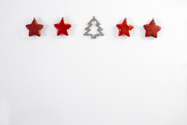 O natal beira-vermelho do natal stars brinquedos da árvore de natal e árvore de natal no fundo branco, bandeira horizontal. cartão de natal ou ano novo. copyspace